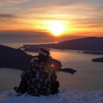 Skiers pause at the top of Cypress Mountain to watch as the sun goes down over the Strait of Georgia in North Vancouver, Canada.