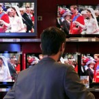 A customer at a television flat screen shop in Paris watches the wedding service of Britain's Prince William and Kate Middleton at Westminster Abbey, Friday April 29, 2011. (AP Photo/Thibault Camus)