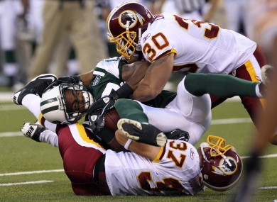 New York Jets wide receiver Braylon Edwards, center, is tackled by Washington Redskins' LaRon Landry (30) and Reed Doughty (37) last season. The sides are slated to meet on 11 September.