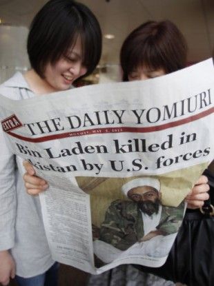 Women reads the extra edition of a Japanese newspaper in Tokyo Monday, May 2, 2011, reporting the death of Osama bin Laden.
