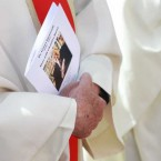 A priest holds a mass card at the funeral mass.