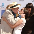 Peter O'Toole plants one on actress Rose McGowan, watched by Anjelica Huston