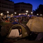 A demonstrator is seen inside his tent as he spends the night in Sol square during a protest in Madrid against austerity measures taken to end Spain's debt crisis. (AP Photo/Emilio Morenatti)