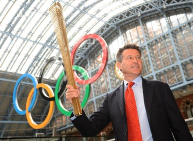 Sebastian Coe holds the newly-designed Olympic torch aloft.