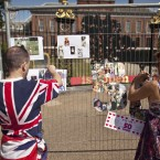 Kathy Martin and John Loughrey put up their Princess Diana 50th birthday tributes on fencing outside Kensington Palace in London (AP Photo/Matt Dunham)