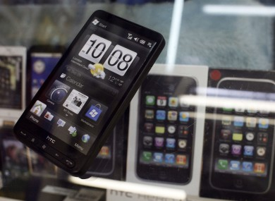 Taiwan's HTC mobile phones are seen on display near Apple Inc's iPhones in a popular computer market in Taipei