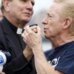 Bob Kriesat, left, and his partner Ed Mather interlock hands as they hold on to the mic of a loud speaker during a gay marriage rally at Pier A Park, yesterday in Hoboken, New Jersey. The couple and others at the rally asked New Jersey officials to pass a law allowing same-sex marriages in the state similar to that in New York. (AP Photo/Julio Cortez)