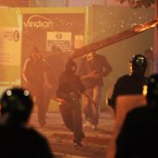 A rioter throws a burning wooden plank at police in Tottenham, north London after members of a community where a young man was shot dead by police took to the streets to demand