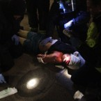 Riot police treat a man for his injuries before arresting him in Tottenham, north London as trouble flared after members of the community took to the streets last night to demand