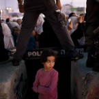 A Palestinian child waits for her mother to cross the Qalandia checkpoint on their way to pray at the Al Aqsa Mosque on the third Friday of the Muslim holy month of Ramadan, Friday, Aug. 19, 2011. 