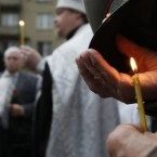 A Russian Orthodox priest prays as Moscovites light candles at a memorial to three men killed in the August 1991 hard line Communist coup attempt during a ceremony marking the 20th anniversary of the failure of the coup in downtown Moscow, Saturday, Aug. 20, 2011. 
