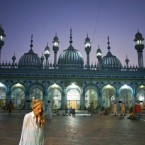 A Pakistani leaves as others offer evening prayers during the Islamic holy fasting month of Ramadan in Rawalpindi, Pakistan on Sunday, Aug. 21, 2011. 