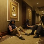 Journalists sit it out in a hallway as gun-battles continue around the Rixos hotel in Tripoli, Libya, Tuesday, Aug. 23, 2011. Dozens of journalists were trapped inside the hotel as forces loyal to Muammar Gaddafi prevented them from leaving and gun battles with rebel forces raged around the building. 