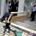 A Libyan expatriate smashes a portrait of embattled Libyan leader Col. Muammar Gaddafi after raising the Libyan rebel flag at the Libyan Embassy at suburban Makati city east of Manila, Philippines. 