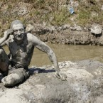 A man covered in mud sunbathes next to a small mineral spring pool in Ovca, a rural suburb of Belgrade, Serbia, Wednesday, Aug. 24, 2011. 