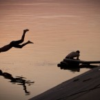A man dives at sunset in a lake at the end of an unusually hot day in Bucharest, Romania, Wednesday, Aug. 24, 2011.
