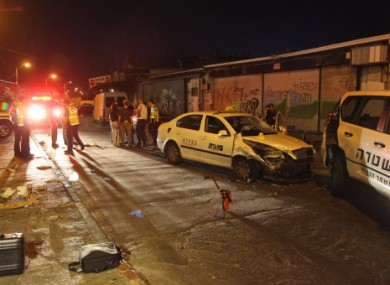 Israeli policemen gather at a site where a Palestinian man crashed a car into a crowed of people and stabbed seven people near a nightclub in Tel Aviv, early Monday, Aug. 29, 2011.