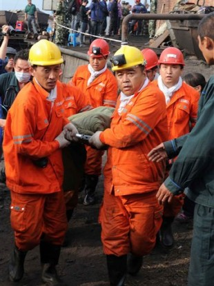 In this photo released by China's Xinhua News Agency, rescuers carry a miner out of a flooded mine in Qitaihe, northeastern China, Tuesday, Aug. 30, 2011.