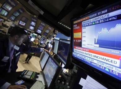 A television screen at the post of specialist Stephen Ruiz, left, displays the decision of the Federal Reserve, on the floor of the New York Stock Exchange