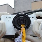 Model Brooke Colman cleans the lens on a super-sized replica of the Nikon 1 J1 which is held by giant hands in Covent Garden, London.