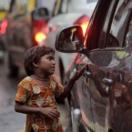 A girl begs to a person sitting in a car on a busy street in Mumbai, India, Wednesday, Sept. 21, 2011. 