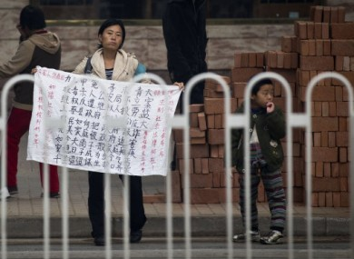 A Chinese petitioner holds a protest banner to seek justice for her dead son near a court house, where jailed activist Wang Lihong attends her court appeal case in Beijing, China, Thursday, Oct. 20, 2011.