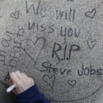 Apolline Arnaud, 12, a neighbour of Steve Jobs, writes a message in front of Jobs' house in Palo Alto, California. (AP Photo/Paul Sakuma)