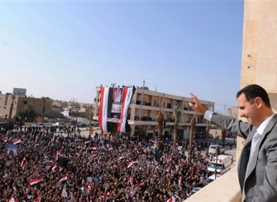 In this photo released by the Syrian official news agency SANA, Syrian President Bashar Assad, right, waves to his supporters on Sunday, Nov. 6, 2011
