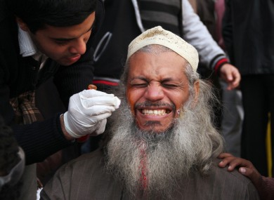 An injured man receives treatment during today's clashes at Tahrir Square.