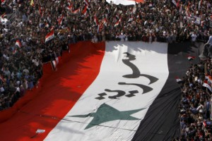 Pro-Syrian regime protesters, carry a giant Syrian flag during a demonstration against the Arab League decision to suspend Syria, in Damascus earlier today. 