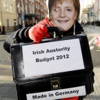 A protestor dressed as German Chancellor Angela Merkel outside Leinster House in Dublin as Finance Minister Michael Noonan prepared to announce the second half of the Budget 2012 detailing major tax reforms. Photo: Niall Carson/PA Wire