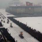 The funeral motorcade including a car exhibiting a large portrait of the late Kim Jong Il drives by the Kim Il Sung Square in Pyongyang on Dec. 28, 2011. (Kyodo)