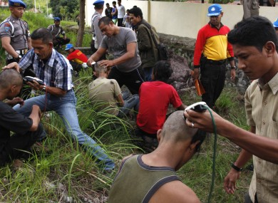 Plain-clothes police officers shaving the heads of punks in Banda Aceh.