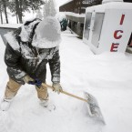 Randy Earheart shovels snow at the Rimrock Lake Resort near White Pass, Washington. (AP Photo/Yakima Herald-Republic, Gordon King)