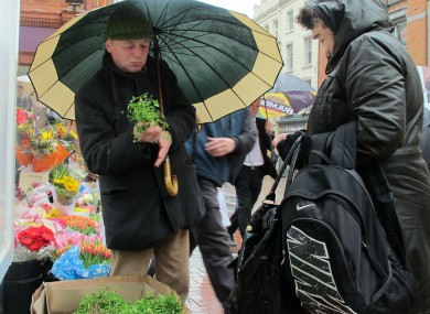 Flower seller Jimmi Lee, 55, sells a sprig of shamrock to shopper Catherine Fahy, 45, in Dublin today.