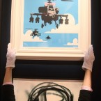 A Bonham's employee adjusts Banksy's Happy Choppers, estimated to fetch 4,000 - 6,000 at Urban Art auction. (Lewis Whyld/PA Images)