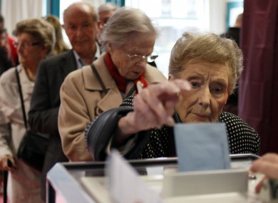 A woman casts her ballot during the first round of the French elections in Lille, northern France, Sunday, April 22, 2012