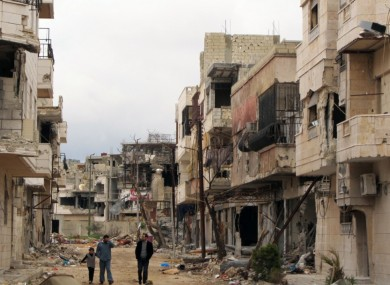 Syrians walk between destroyed buildings in the Inshaat neighborhood of Homs, Syria