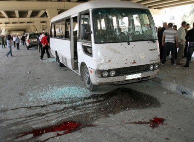 Syrian investigators, right, gather next to a damaged police bus that was attacked by an explosion in the Midan neighborhood of Damascus, Syria, on Friday April 27, 2012