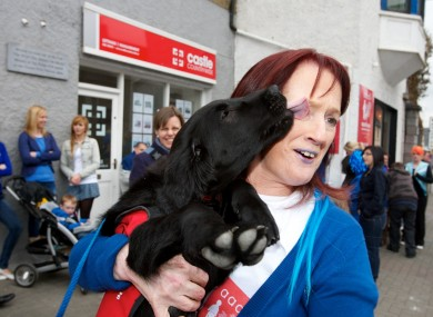 Assistance puppy dog 'Skye' gives Breeda Clancy of AADI a big kiss turning Mallow Blue for World Autism Awareness Day at the Autism Assistance Dogs of Ireland HQ.