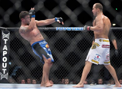Frank Mir, left, falls backward after Junior Dos Santos landed a punch in the second round.