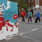 People walk past a defaced sign against the European Fiscal Treaty in Dublin, ahead of tomorrows referendum. 
