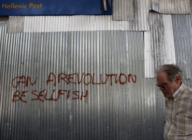 A Greek man walks past metal sheeting sprayed with a slogan in English reading 