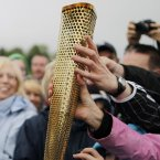 People touch the Olympic Torch on the border crossing.