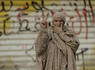 A Bahraini pro-democracy protester gestures in front of a wall sprayed with anti-government graffiti