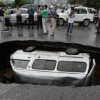 A van is trapped in a hole after a cave-in happened at Fuxing road in Guilin, Guangxi Province. (Photo by He Zhiqin/ChinaFotoPress/PA)