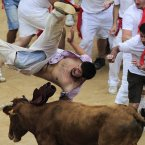 A reveler is tossed by a cow in the bull ring at the end of third running of the bulls at the San Fermin fiestas in Pamplona, northern Spain. (AP Photo/Alvaro Barrientos)