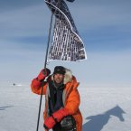 Mark at the South Pole with his flag containing the images of those who sponsored him