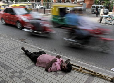 An Indian man sleeps on a pavement as traffic moves past in Ahmadebad.
