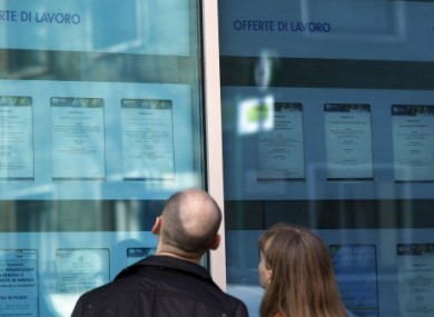 A couple checks jobs offers on the window of an employment agency in Milan.